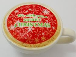 カフェラテにクリスマスのデザインを印刷した透明可食シートをのせてラテアート風に